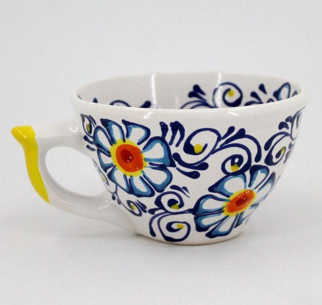 Getöpferte Tasse mit Blumenmuster bemalt
