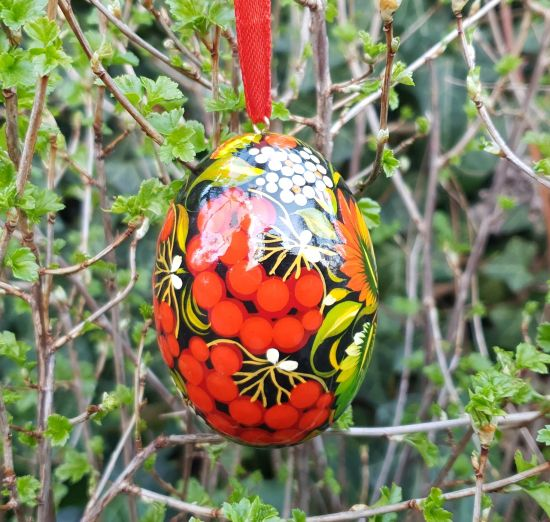 Black wooden Easter egg pysanka painted with red barries