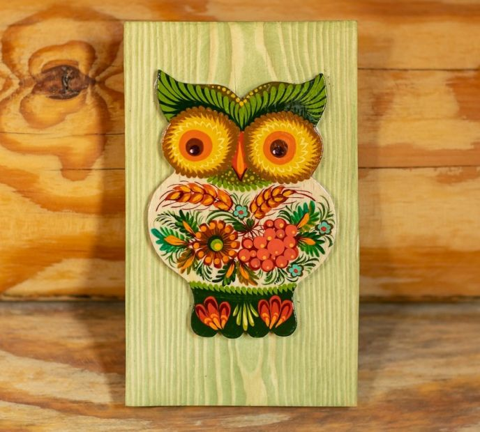 Rustic wall decoration made of wood owl on the green