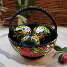 Traditional painted Easter eggs in a small wooden basket