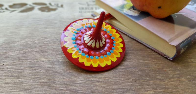 Spinning top, traditional wooden toy with geometric ornament, hand painted