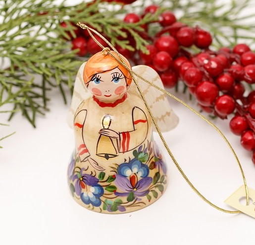 Christmas angel with little wings and a bell in hands